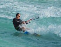 Drachen-Internatsschüler, der die Ozean-Schnitte und die Sprays surft stockfoto