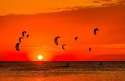 Drachen-Surfen gegen einen schönen Sonnenuntergang Viele Schattenbilder der Ausrüstung Stockbild