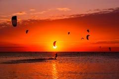 Drachen-Surfen gegen einen schönen Sonnenuntergang Viele Schattenbilder der Ausrüstung Stockfoto