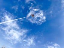 Drachenfliegen in einem blauen Himmel mit einem furchtsamen Wolkenschädel stockfotografie