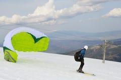 Drachenskifahrer, der weg vom Gebirgsrücken fliegt lizenzfreies stockbild