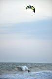 Drachensurfer, die auf dem Meer kitesurfing sind Stockfotografie