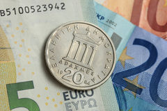 Drachma coin on euro note Stock Image