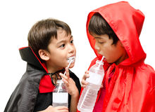 Dracula and the boy with the red hood halloween costume drinking Royalty Free Stock Photos