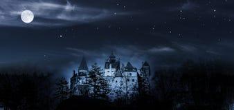 Dracula slott i nichten med fullmånen royaltyfri foto