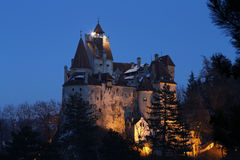 Travel Romania: Bran medieval castle. Late blue hour found me gazing at Romanias most famous castle from the hill in the vicinity. You probably heard of its Stock Photos