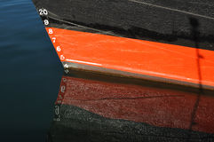 Draft Markings on red and black boat. In the ocean stock photography