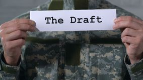The Draft written on paper in hands of male soldier, military duty, closeup. Stock footage stock video footage