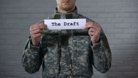 The draft written on sign in soldier hands, compulsory military service, duty. Stock footage stock video footage