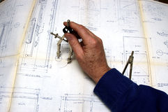 Drafting. A draftsman using a compass on a blueprint Royalty Free Stock Images