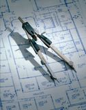 Drafting Compass on Blueprint. A drafting compass on a blue print of an architectural plan Royalty Free Stock Photos