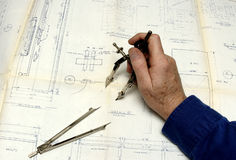 The Draftsman. Drafysman working on a drawing with compass and dividers Royalty Free Stock Images