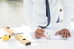 Draftsman. Cropped image of a professional draftsman correcting a blueprint stock photos