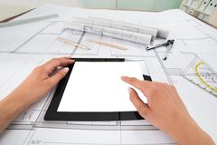 Draftsman with digital tablet and blueprint. Draftsman Hands With Blank Digital Tablet Over Blueprint In Office. Blueprints were created by photographer royalty free stock photography