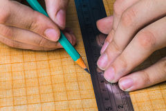 Draftsman draws on a ruler. On the graph paper stock photos