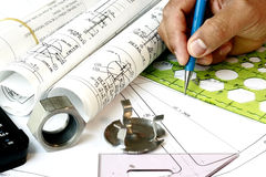 Draftsman with engineering plans. And mechanical parts royalty free stock photo