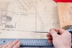 Draftsman working on drawings. A view of the hands of a draftsman or engineer working with detailed drawings or blueprints royalty free stock photo