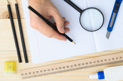 Draftsman workplace equipped with ruler, pen, stapler, scissors, magnifying glass. Closeup hands of man holding pencil and drawing on white paper in top view royalty free stock photography