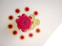 Dragão vermelho do fruto em um fundo branco perto do cal verde e dos biscoitos frescos Pequeno almoço tropical Fotos de Stock