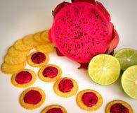 Dragão vermelho do fruto em um fundo branco perto do cal verde e dos biscoitos frescos Pequeno almoço tropical Foto de Stock Royalty Free