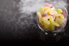 Dragées à la gelée de sucre aigres dans la tasse en verre Photo libre de droits