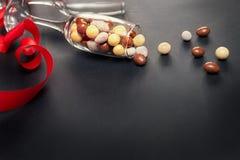 Dragées de chocolat, verre et ruban rouge pour le jour de valentines Photo stock