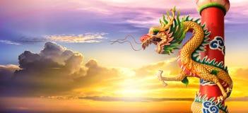 Dragón chino de oro en la puesta del sol en el fondo crepuscular Imagen de archivo libre de regalías