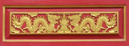 Dragón de oro adornado en la pared roja Foto de archivo