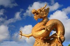 Dragón de oro con el cielo azul claro Imagenes de archivo