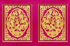 Dragón de oro tallado adornado en puerta de madera roja Fotos de archivo