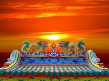 Dragón doble en el tejado chino y la puesta del sol del templo Foto de archivo