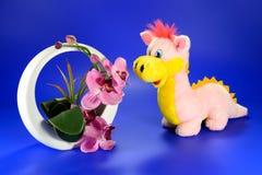 Dragón rosado con un florero decorativo de flores Imagen de archivo libre de regalías