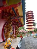 Dragões e leões dourados gêmeos no templo com a torre vermelha e amarela do fundo do pagode Ekayana foto de stock royalty free