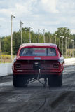 Drag racing. Rear view of red chevrolet vega drag car making a wheelie on the track Royalty Free Stock Photos