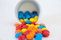 Drag?es rondes multicolores de sucreries renvers?es hors d'une tasse de papier invers?e image stock