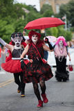 A Drag Queen Runs the streets in the Gay Pride Parade. Taken in Des Moines - 2015. The gay pride parade sports participants running in the parade with umbrellas stock images