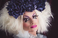 Drag queen with spectacular makeup, glamorous. Trashy look, posing happily and charming camera from sideways angle Stock Photography