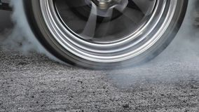 Drag racing car burn tires at start line. Drag racing car burns rubber off its tires in preparation for the race stock footage