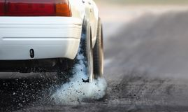 Drag racing car burns rubber off its tires in preparation for the race. At start line stock photos