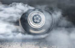 Drag racing car burns rubber off its tires in preparation for the race stock images