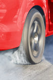 Drag racing car burns rubber off its tires Stock Images