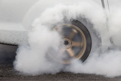 Drag racing car burns rubber off its tires. In preparation for the race Royalty Free Stock Image