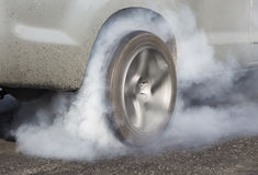 Drag racing car burns rubber off its tires Stock Photography