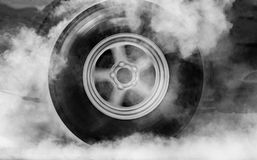 Drag racing. Car burns rubber off its tires in preparation for the race stock images