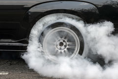 Drag racing car burns rubber off its tires for the race Stock Images