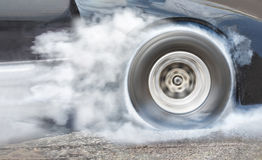 Drag racing car burns rubber off its tires for race. Drag racing car burns rubber off its tires in preparation for the race stock photography