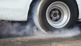 Drag racing car burns tire for the race. Drag racing car burns rubber off its tires in preparation for the race stock footage