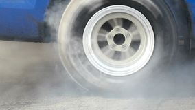 Drag racing car burns tires for the race. Drag racing car burns rubber off its tires in preparation for the race stock video