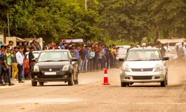 Drag racing on a dirt track in Delhi. Delhi, India; 14th Mar 2015 - Crowd of people watching a couple of cars drag racing on a dusty road in Delhi. This was one Stock Image