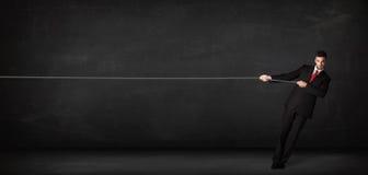Dragande rep för affärsman på grå bakgrund Royaltyfri Bild